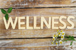 Quadro Wellness written with wooden letters, chamomile flowers on wood