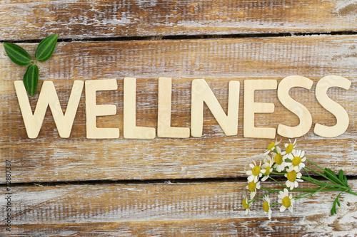 Leinwanddruck Bild Wellness written with wooden letters, chamomile flowers on wood
