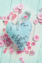 Heart and buttons on wooden background
