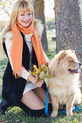 Attractive girl with her dog wearing warm clothes