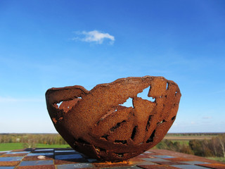 Rusted bowl with blue sky as background