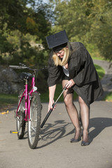 Mature student wearing cap and gown inflating cycle tyre