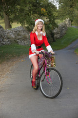 Woman in Santa outfit riding bicycle