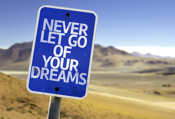 Never Let Go Of Your Dreams sign with a desert