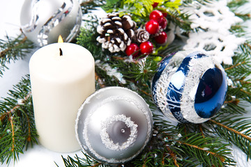 Christmas accessories in blue & fir tree branch on white