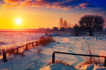Winter snowy rural landscape at sunset