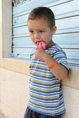 Child with ice cream lolly at street