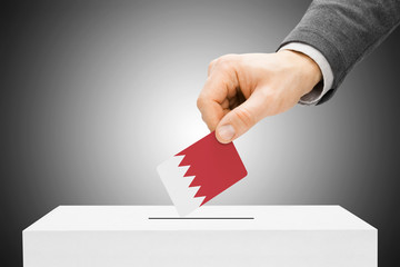 Voting concept - Male inserting flag into ballot box - Bahrain