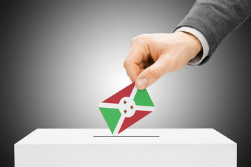 Voting concept - Male inserting flag into ballot box - Burundi