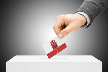 Voting concept - Male inserting flag into ballot box - Gibraltar