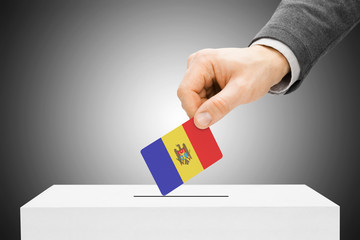 Voting concept - Male inserting flag into ballot box - Moldova