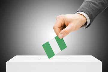 Voting concept - Male inserting flag into ballot box - Nigeria