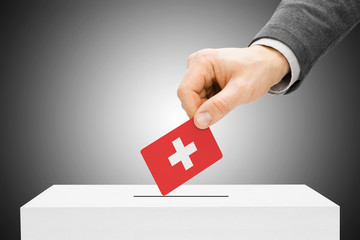 Male inserting flag into ballot box - Switzerland