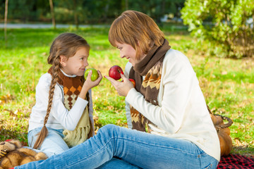 Happy mother with little daughter in autumn park