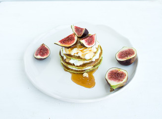 Marrow pancakes with fresh figs, honey and goat cheese on a whit