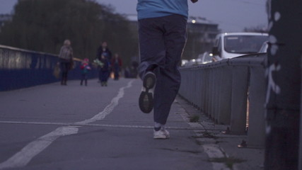 Man jogging by the street in the city in the evening, super slow