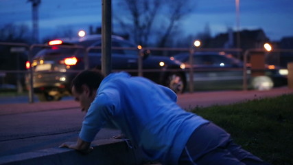 Young man doing push ups in the city at night