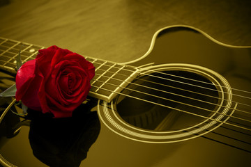 Acoustic black guitar and red rose