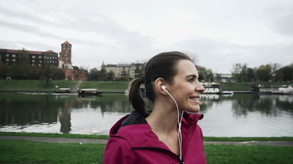 Portrait of young happy female jogger in the city, super slow mo