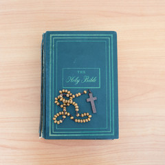 cross of rosary beads on the bible.