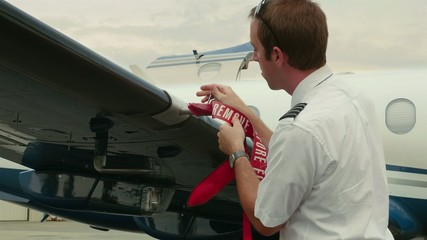 Pilot Attaches Post-Flight Safety Covers Ribbons to Back of Wing
