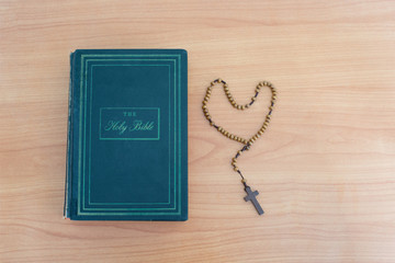 Cross of rosary beads and bible on the table.