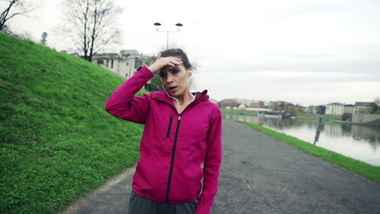 Tired woman resting after jogging in city