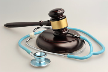 Stethoscope with judge gavel on gray