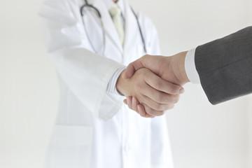 握手する医師とビジネスマンの手