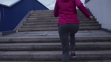 Woman jogging up the stairs in city