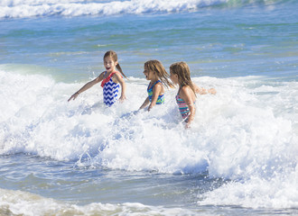 Kids playing in the ocean surf on vacation