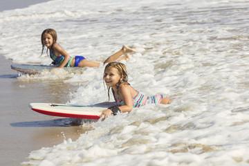 Cute little girls boogie boarding in the ocean waves