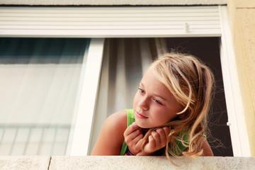 Little blond Caucasian girl in the window, outdoor portrait