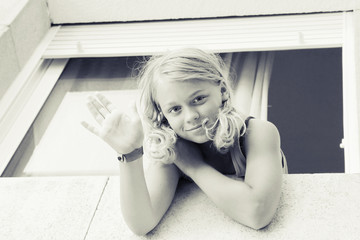 Young blond girl showing hello gesture in the window