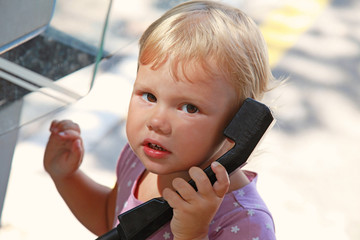 Outdoor portrait of little blond girl talking on street phone