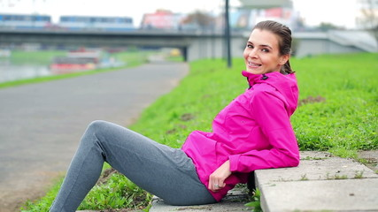 Portrait of young happy female jogger relaxing on stairs in city