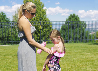 Mother Applying Sunscreen on her daughter outdoors