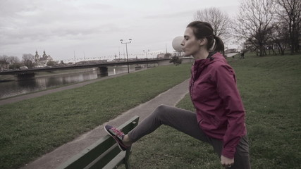 Woman stretching leg before jogging, super slow motion, shot at