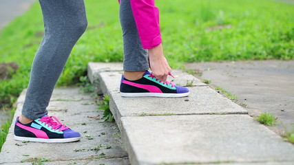 Female jogger tying shoelace in running shoe during jogging