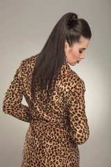fashion woman wearing a animal print coat looking down