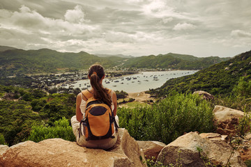 Woman traveler sits and looks  at the edge of mountains