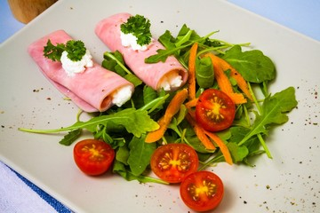 Rolled slices of ham filled with horseradish cream on plate