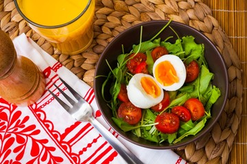 Ruccola salad with tomatoes, egg, orange juice