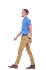 side of casual young man walking