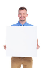 casual young man shows his blank board