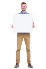 casual young man holds blank board