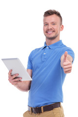 casual young man with tablet shows thumb up