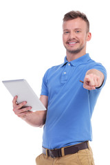 casual young man holds his tablet and points