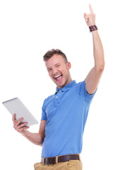 casual young man with tablet cheers