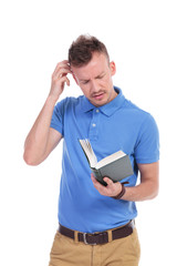 young casual man holds book and thinks